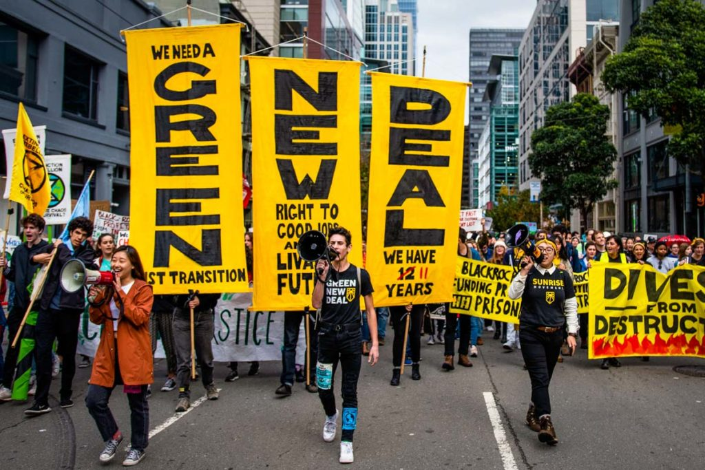 A large group of climate activists during the December 2019 Climate Strikes. Large yellow Green New Deal vertical signs are the most prominent signs behind three activists leading the march with megaphones.