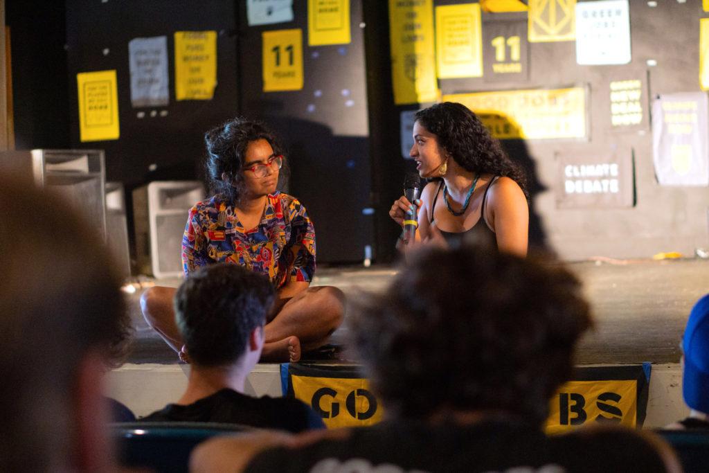 Aru y Varshini se sientan en un escenario mientras participan en una discusión, con varios carteles de arte del amanecer detrás de ellos.