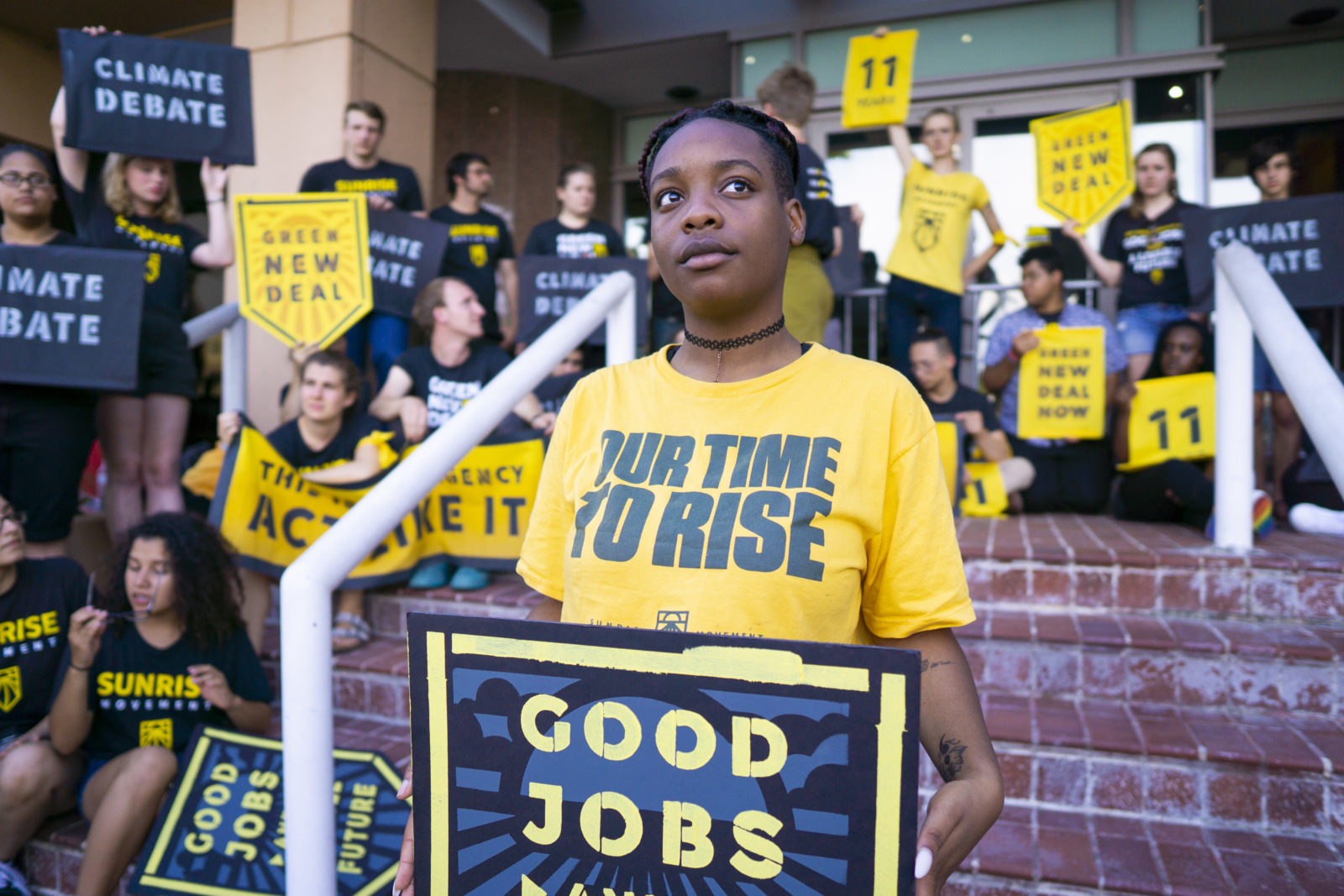 "A Sunrise activist holds a ""Good Jobs For All"" sign and a ""Our Time To Rise"" shirt while fellow protesters occupy the entrance to the DNC headquarters in DC."