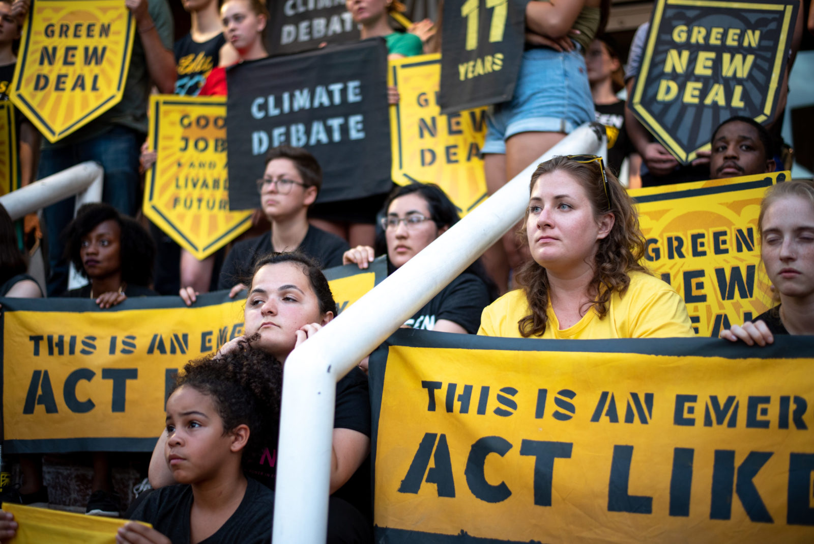 "Sunrise activists completely occupy the entrance to the DNC headquarters in DC. They are sitting on the front steps holding signs saying ""Climate Debate"", ""This Is An Emergency. Act Like It"" and ""Green New Deal""."