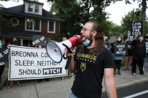 """A Sunrise activist speaks into a megaphone while fellow protesters stand in front of Mitch McConnell's KY house holding a large sign saying """"Breonna Couldn't Sleep. Neither Should Mitch""""."""