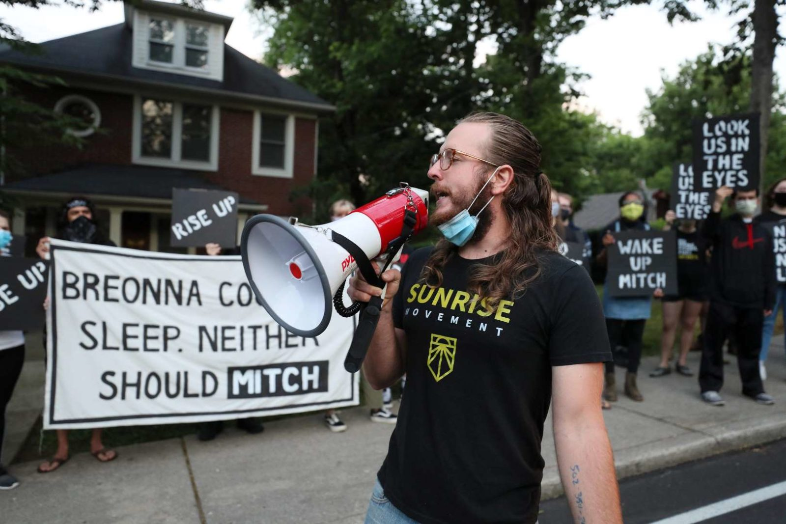 "A Sunrise activist speaks into a megaphone while fellow protesters stand in front of Mitch McConnell's KY house holding a large sign saying ""Breonna Couldn't Sleep. Neither Should Mitch""."