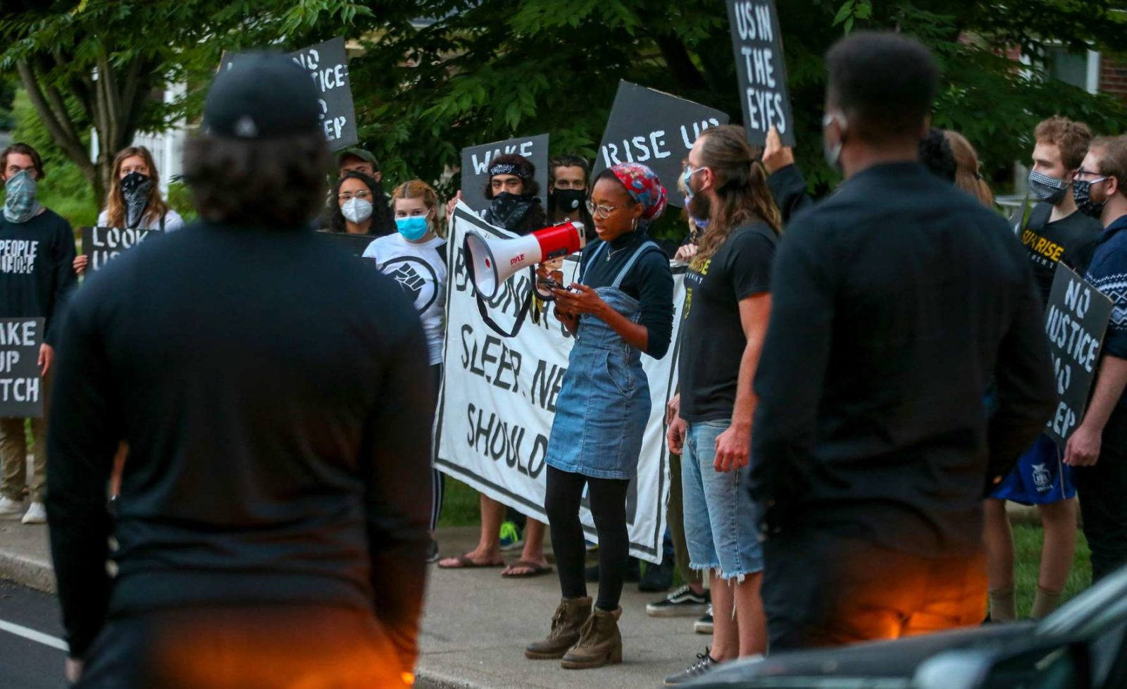 A Sunrise activist speaks into a megaphone while fellow protesters stand in support.