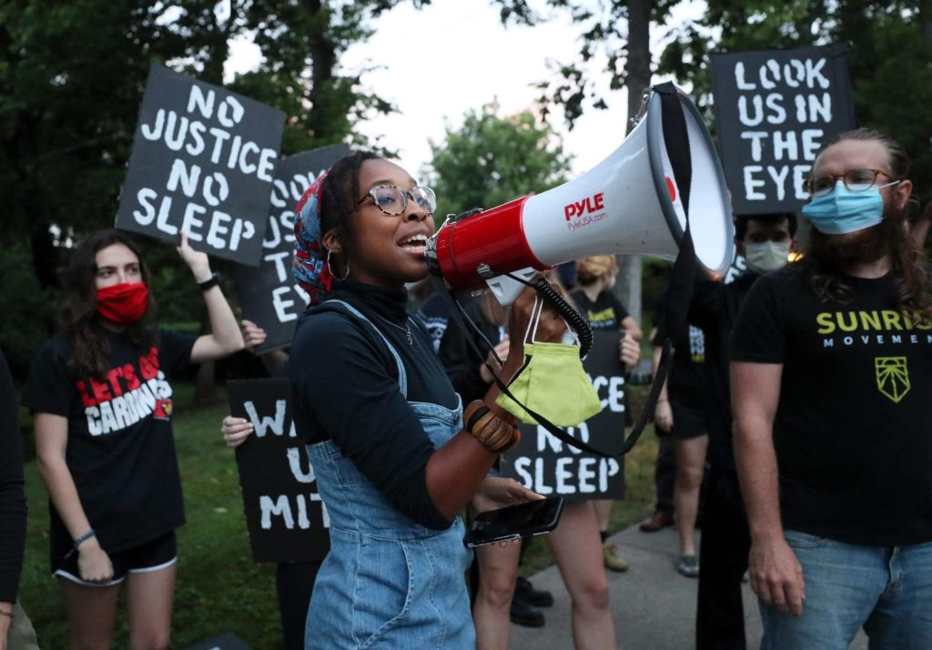 "A Sunrise activist speaking into a megaphone during a 2020 ""Wide Awake"" action in KY, with masked people holding signs saying ""No Justice No Sleep"" and ""Look Us In The Eye""."