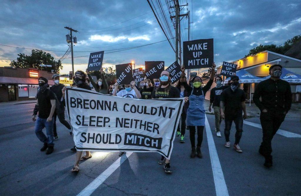 """Los activistas de Sunrise ocupan la calle mientras marchan hacia la casa de KY de Mitch McConnell mientras sale el sol. Llevan un gran cartel que dice """"Breonna no pudo dormir. Tampoco debería Mitch""""."""