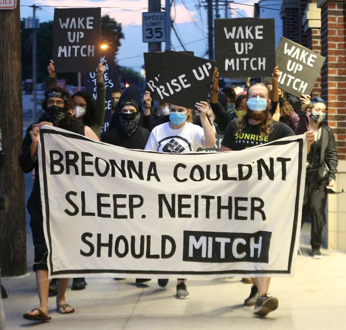 """Sunrise activists march down the sidewalk towards Mitch McConnell's KY house as the sun is rising. They're holding a large sign saying """"Breonna Couldn't Sleep. Neither Should Mitch""""."""