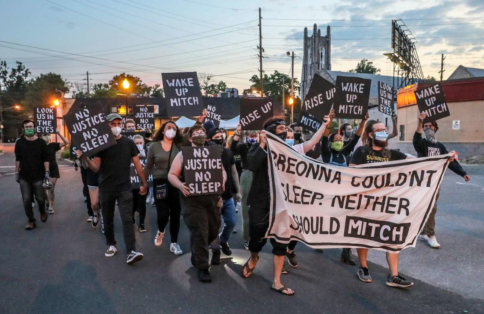 "Sunrise activists march down the street towards Mitch McConnell's KY house as the sun is rising. They're holding a large sign saying ""Breonna Couldn't Sleep. Neither Should Mitch""."