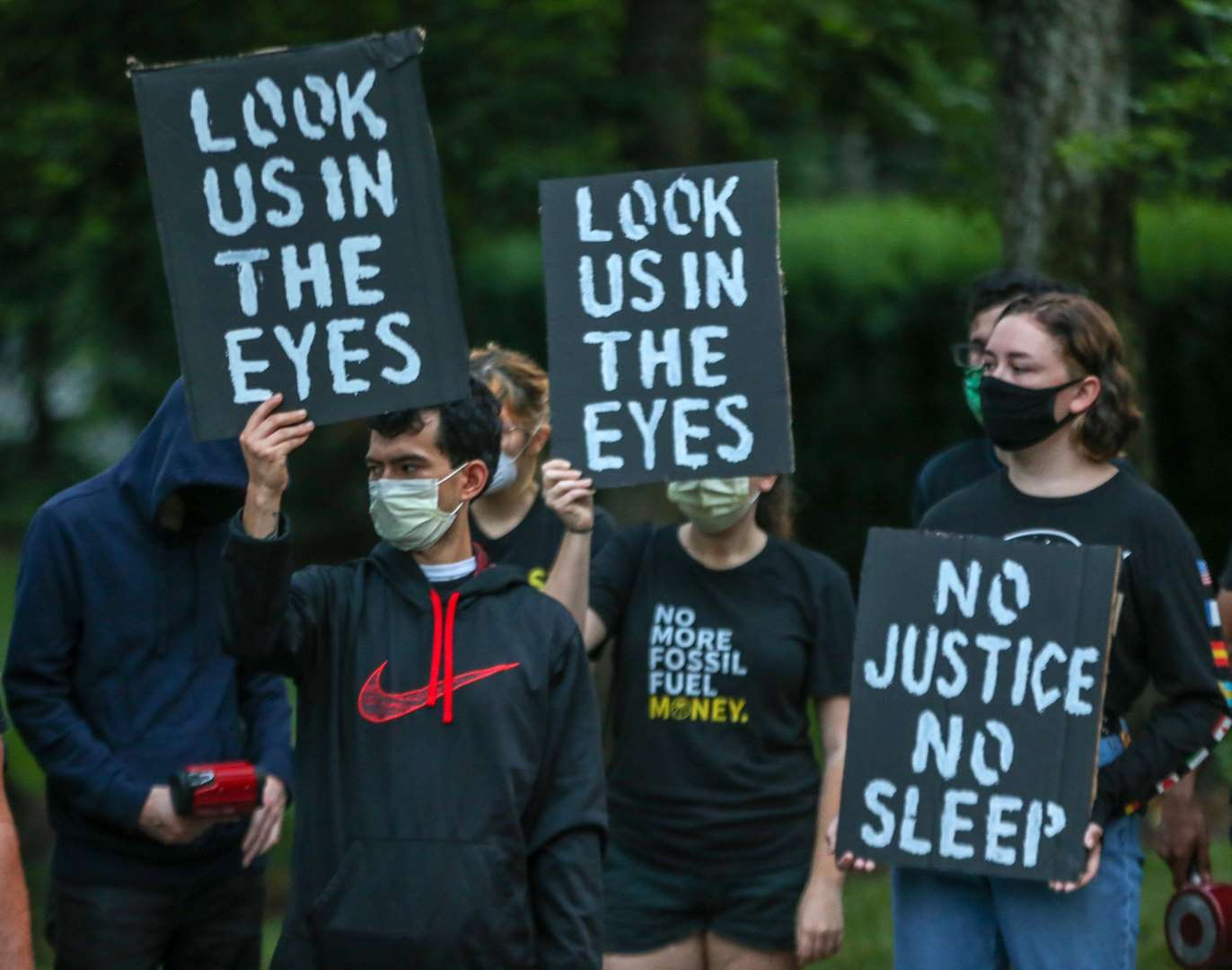 "Protesters hold signs saying ""No Justice No Sleep"", and ""Look Us In The Eyes""."