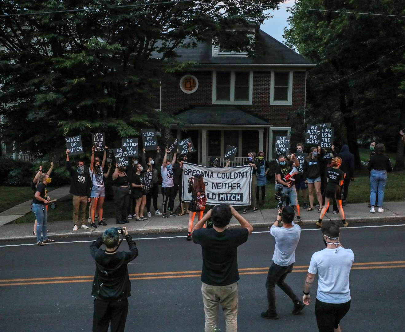 "Sunrise activists fill the sidewalk in front of Mitch McConnell's KY house, holding a large sign saying ""Breonna Couldn't Sleep. Neither Should Mitch""."