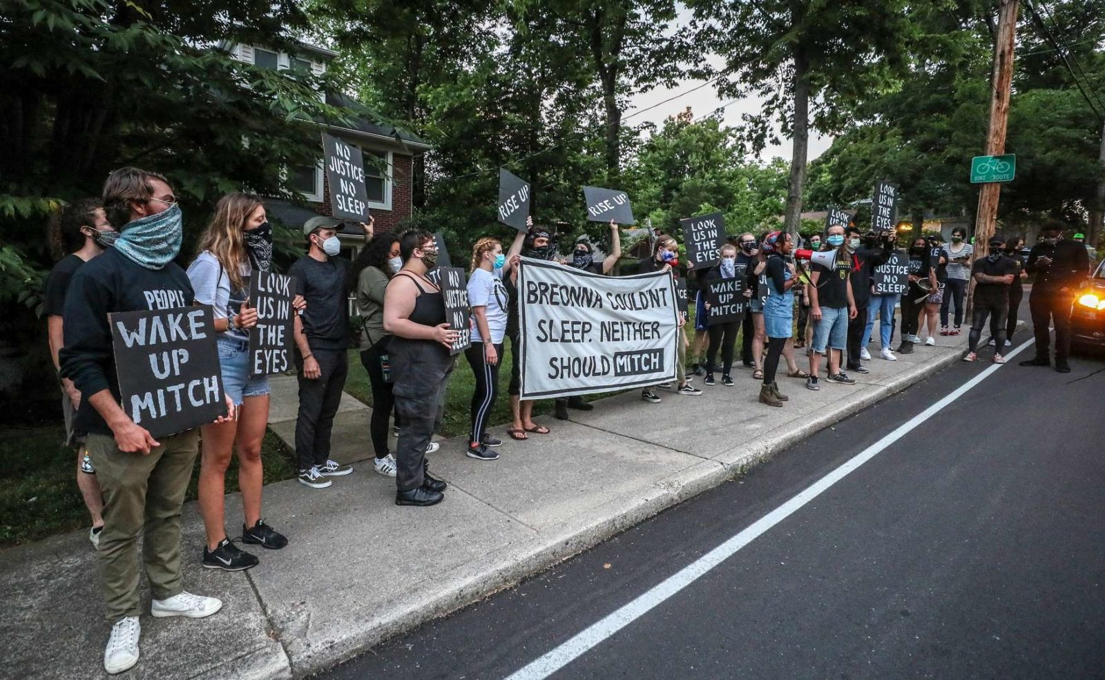 "Sunrise activists line the sidewalk of Mitch McConnell's KY house, holding a large sign saying ""Breonna Couldn't Sleep. Neither Should Mitch""."