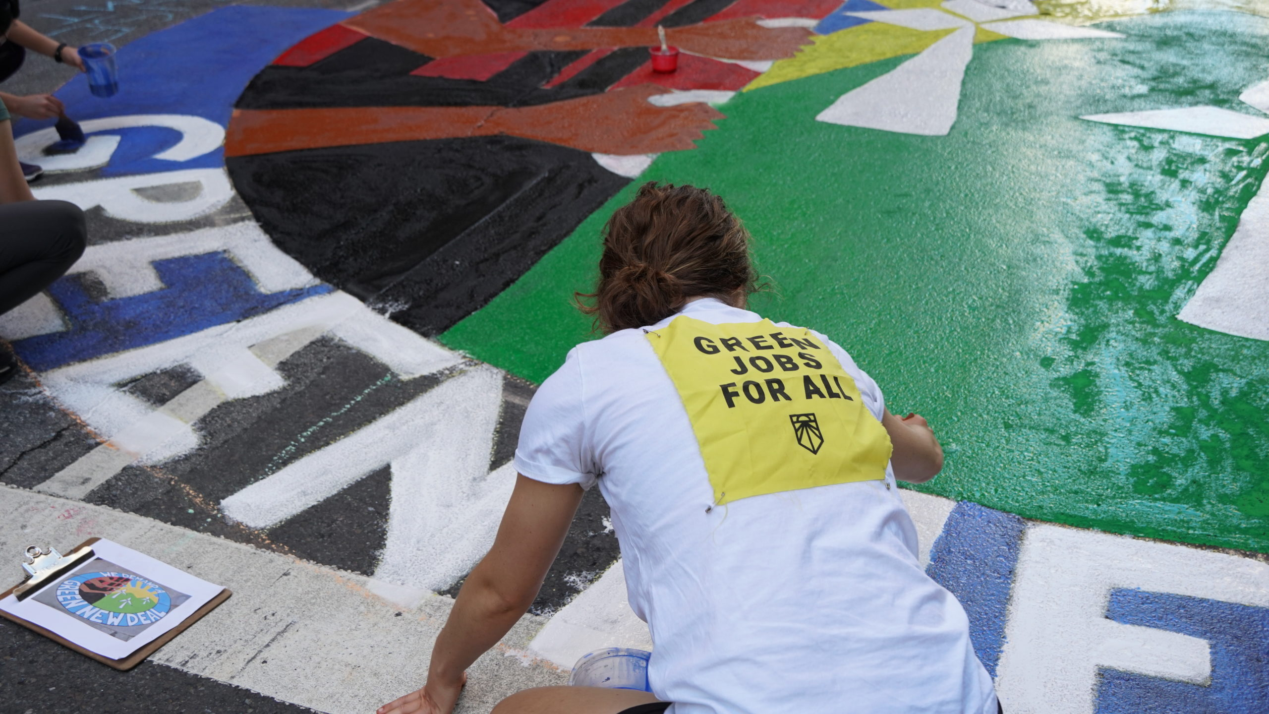 An activist helps to paint a floor mural of the Green New Deal during the September 2019 Climate Strike.