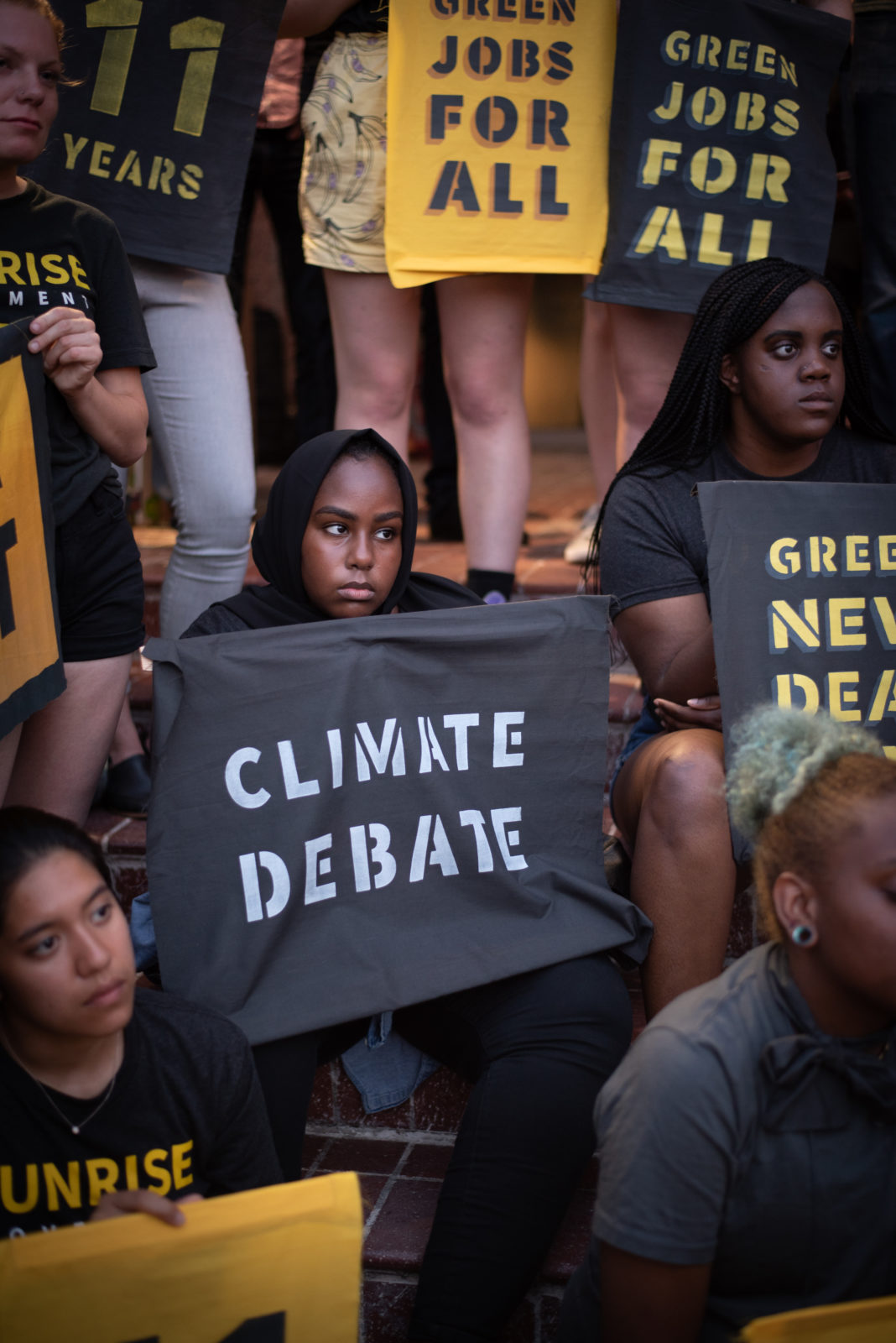 "A Sunrise organizer sits on the steps of the DNC headquarters holding a ""Climate Debate"" sign. She is surrounded by fellow protesters participating in the sit-in."