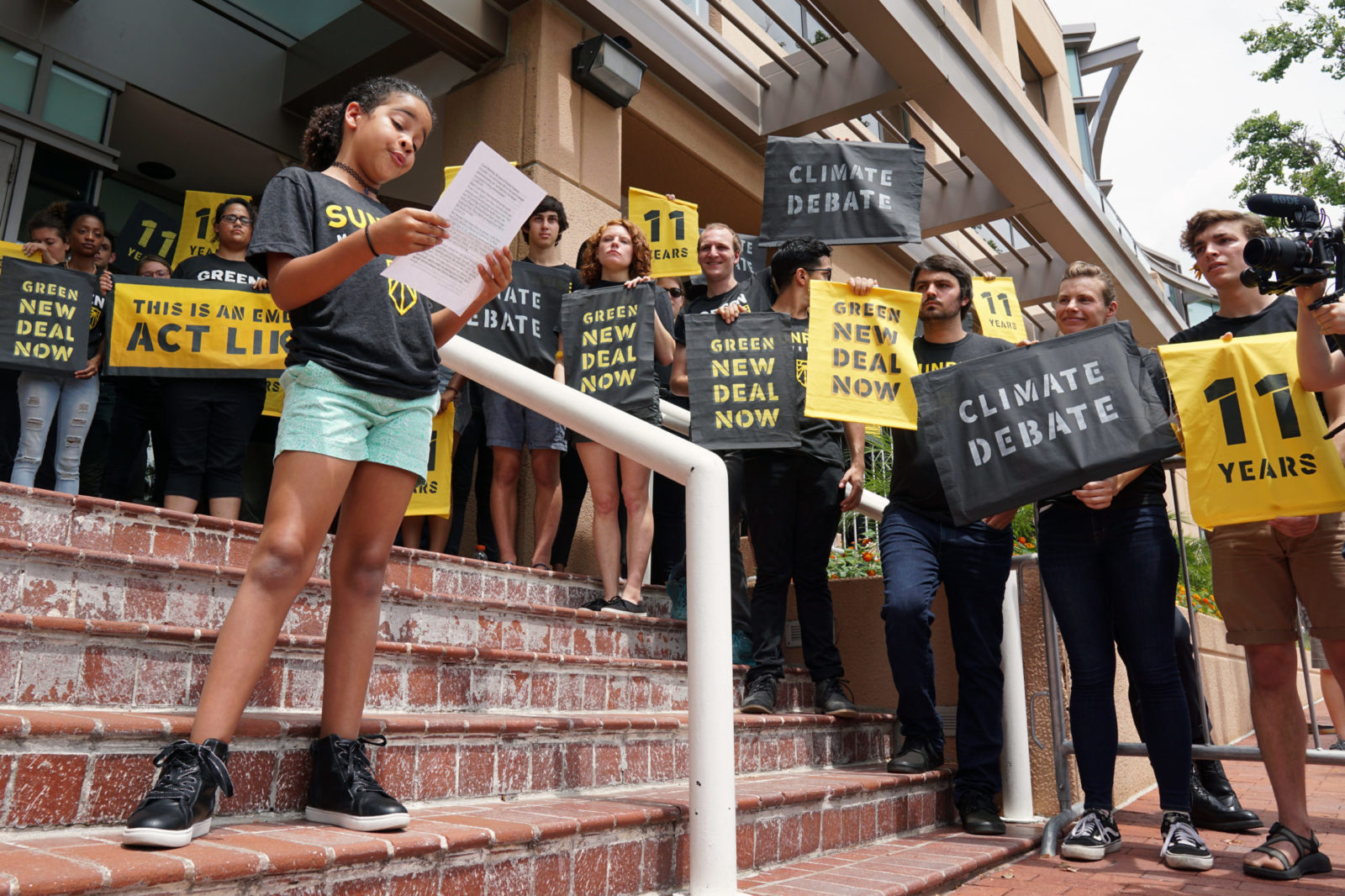 A young Sunrise leader gives a speech while being surrounded by fellow Sunrisers who occupy the entrance to the DNC headquarters in DC to demand a presidential climate debate.