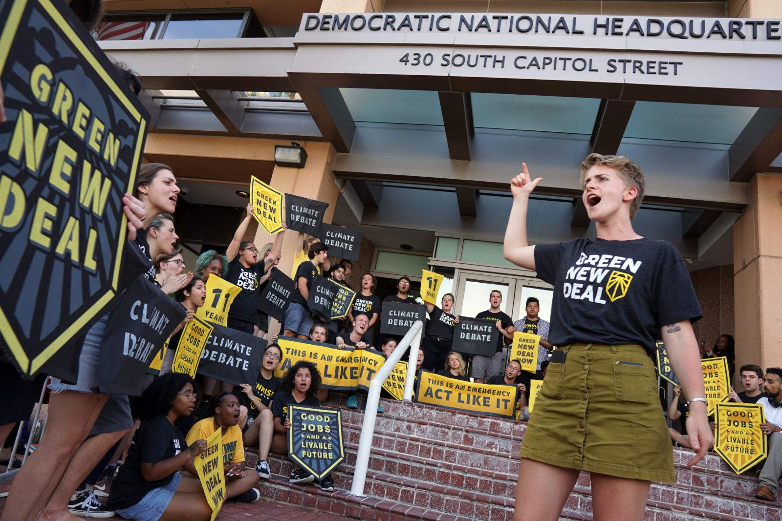 A Sunrise organizer leads a large group of fellow Sunrisers in a song while they occupy the entrance to the DNC headquarters in DC.