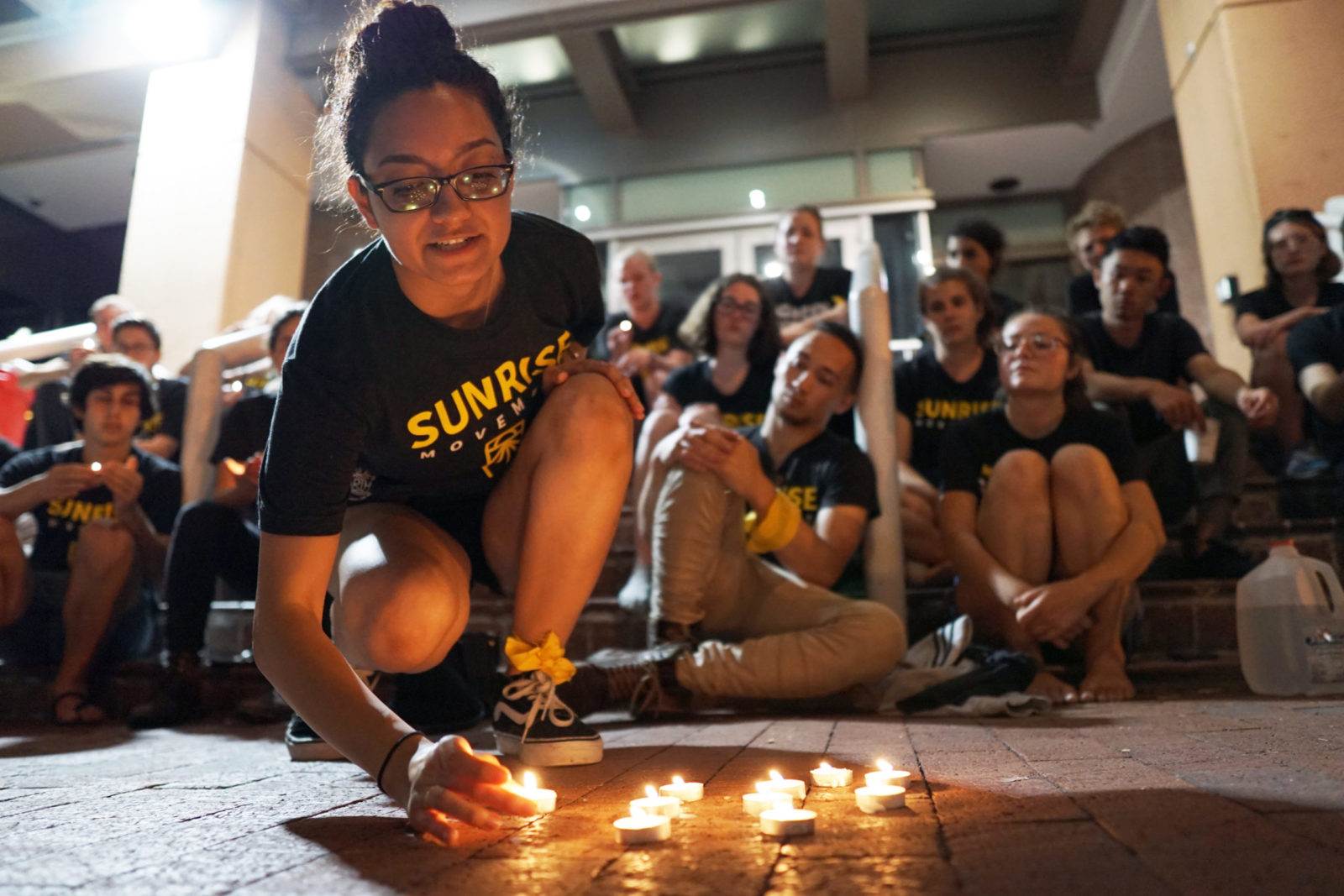 A Sunrise organizer lights candles on the sidewalk in front of the DNC headquarters in DC as protesters prepare for their first night camping out as part of the sit-in.