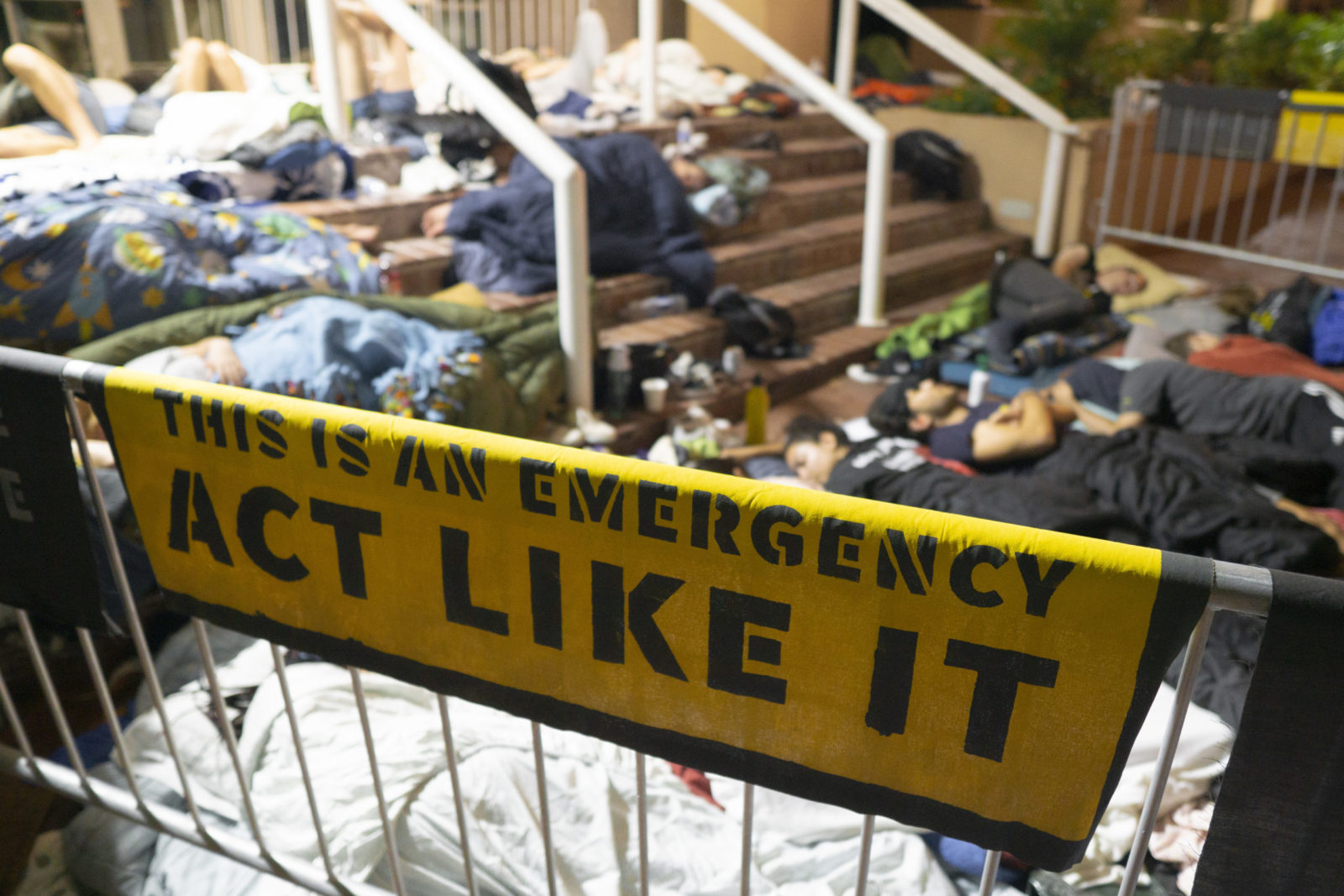 """A """"This Is An Emergency. Act Like It"""" banner is in the foreground as activists camp overnight outside the DNC headquarters in DC."""