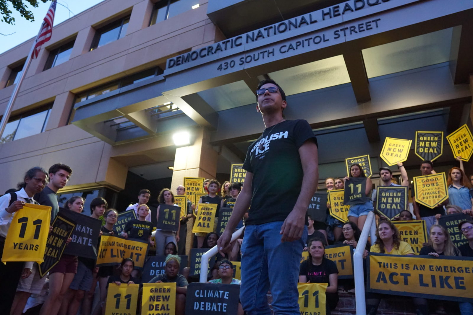 A Sunrise leader gives a speech while being surrounded by fellow Sunrisers who occupy the entrance to the DNC headquarters in DC to demand a presidential climate debate.