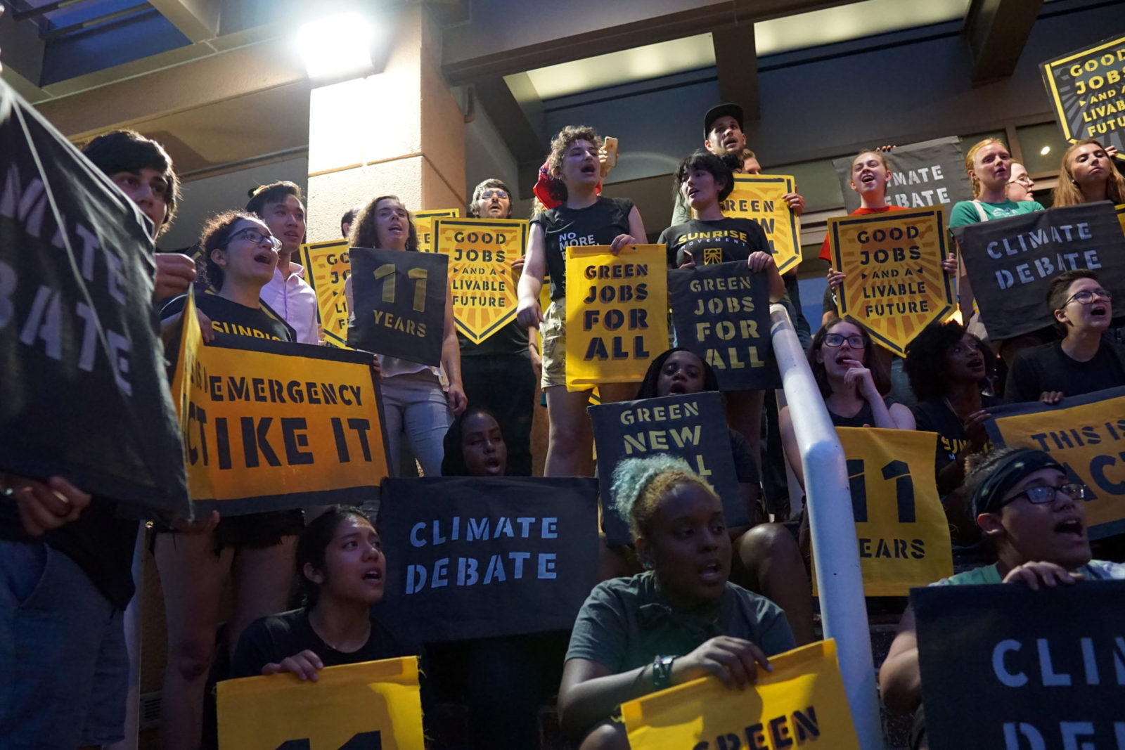 "Sunrise Movement activists completely occupy the entrance to the DNC headquarters in DC. They are singing and holding signs saying ""Climate Debate"", ""This Is An Emergency. Act Like It"", ""Green New Deal"", ""Green Jobs For All"", among others."