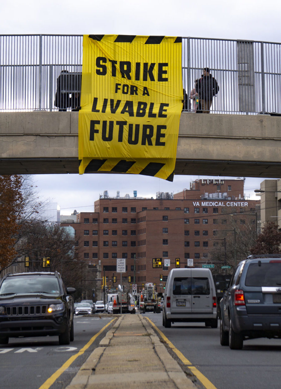 """A """"Strike for a Livable Future"""" banner drop action on a busy street for the December 2019 Climate Strike."""