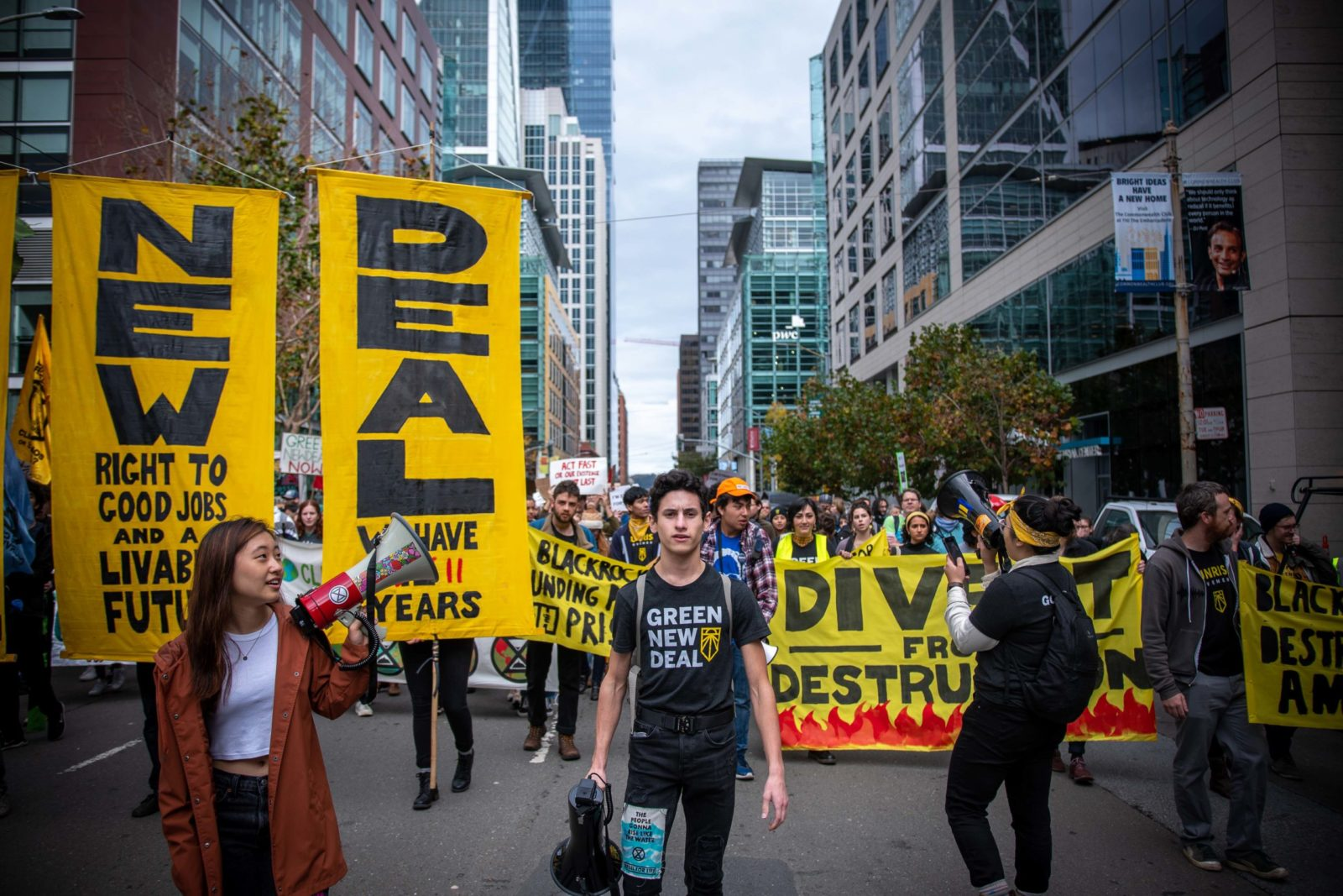 A large group of climate activists during the December 2019 Climate Strikes. Large yellow Green New Deal vertical signs are the most prominent signs.