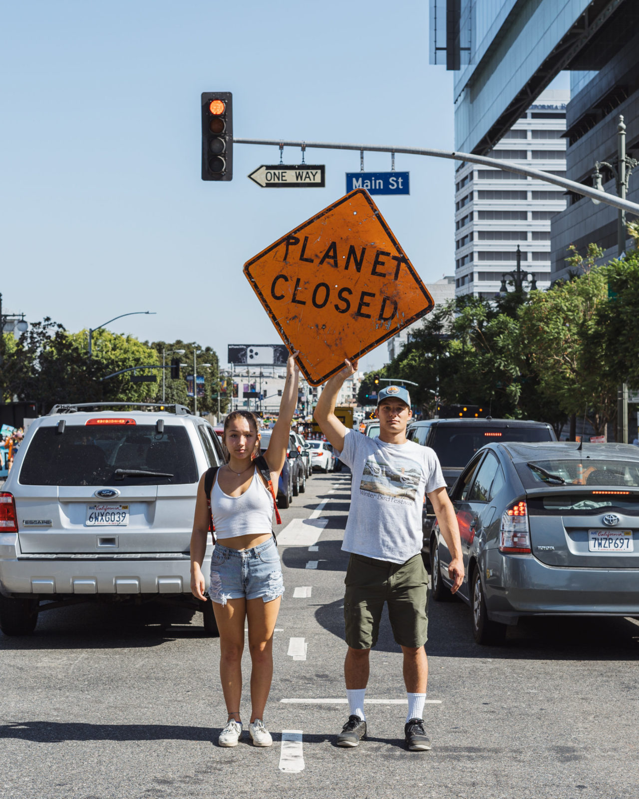"Two people hold a sign saying ""Planet Closed"" in the middle of the street."