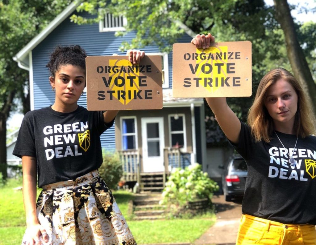 """Image link to Pledge to Vote: Two people holding """"Organize. Vote. Strike."""" signs outdoors."""