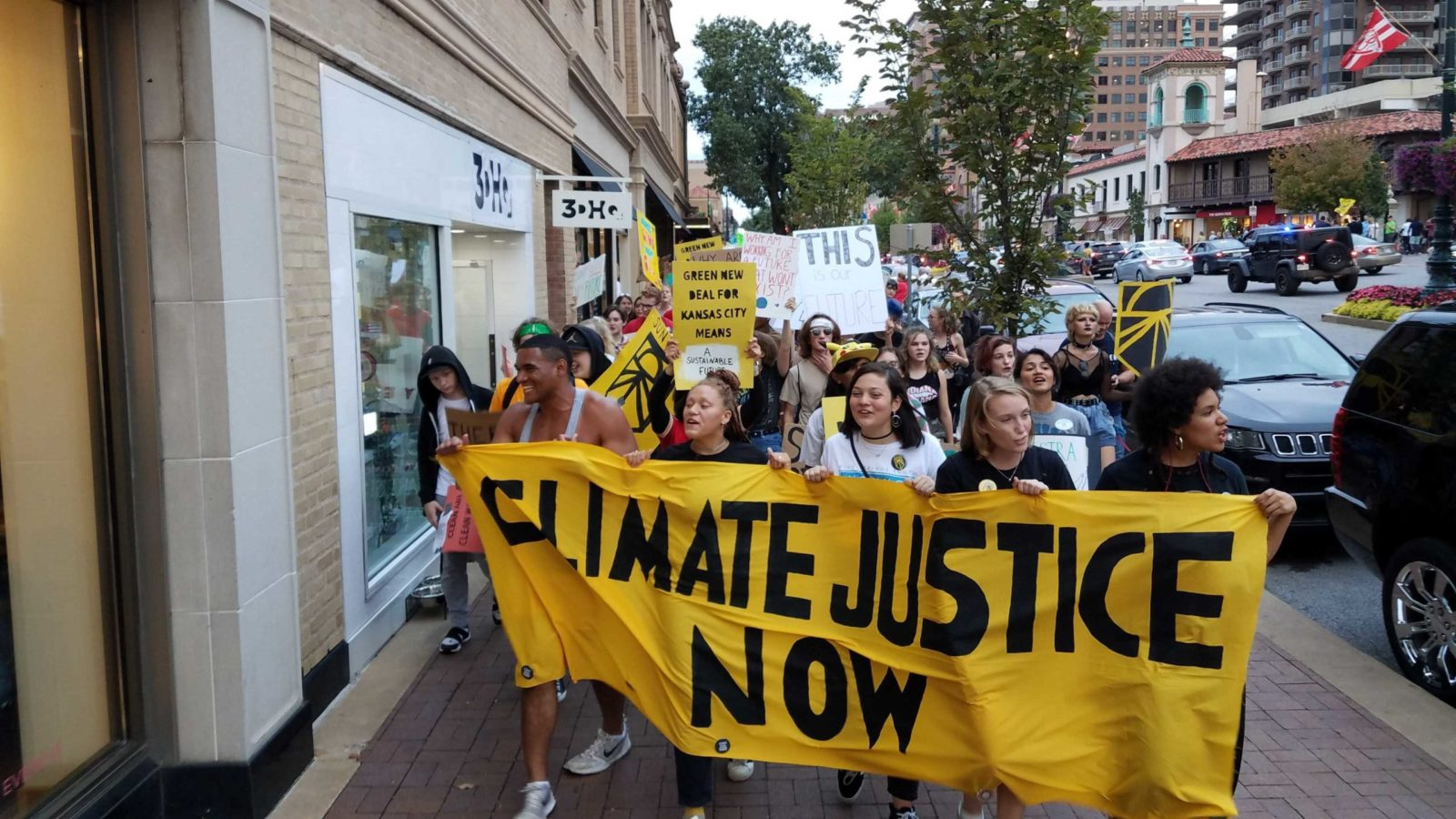 "Activists carry a ""Climate Justice Now"" banner during the September 2019 Climate Strike."