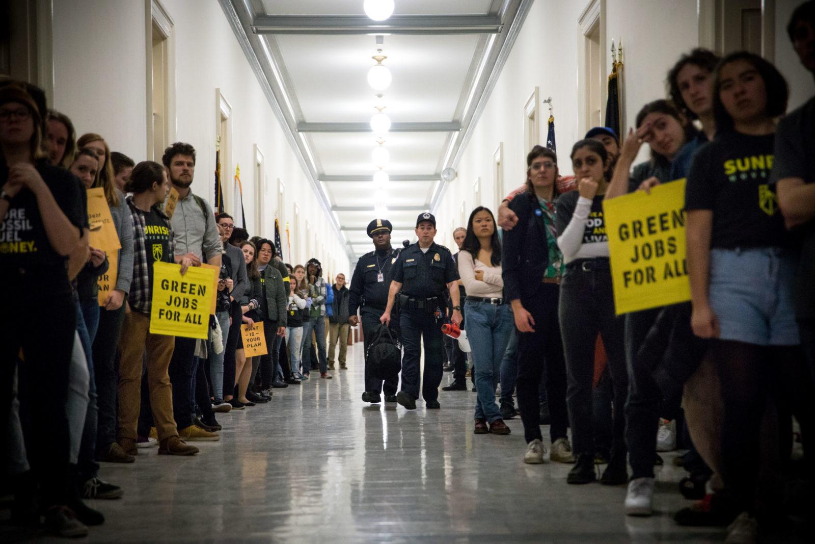 """Los activistas se alinearon en los pasillos del Congreso durante la sentada de noviembre de 2018 en la oficina de Nancy Pelosi para exigir un Green New Deal. Los agentes de policía caminan por los pasillos entre filas de activistas mientras la gente sostiene carteles que dicen """"Empleos verdes para todos""""."""