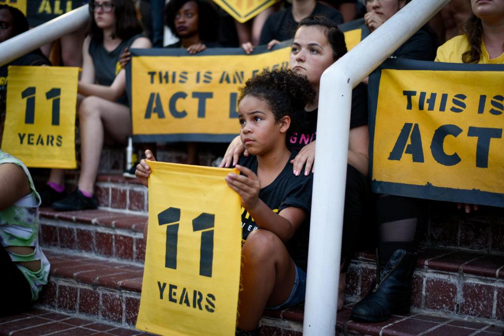 """Un joven activista de Sunrise se sienta en las escaleras de la sede del DNC en DC, sosteniendo un cartel de """"11 años"""". Está rodeada de compañeros activistas."""