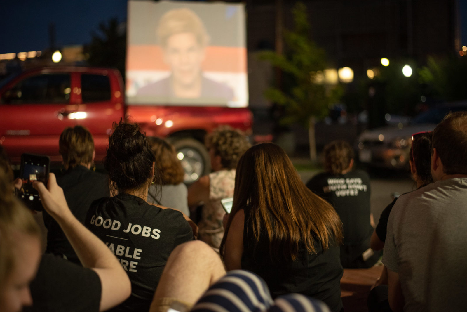 A group of people watch the presidential debate on a screen outside the DNC headquarters in DC during the sit-in.