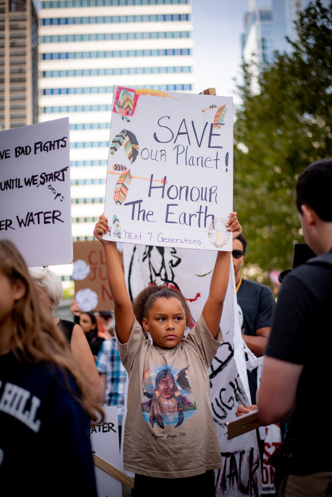 "A young activist holds a sign saying ""Save our planet. Honour the Earth"" during the September 2019 Climate Strike."