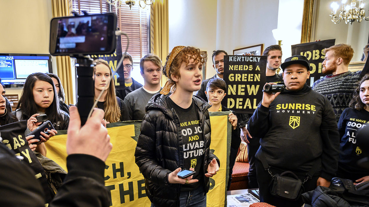 Young Sunrise Movement organizer speaks to cameras in front of crowd holding Green New Deal Banners. Photo by Ken Schles.