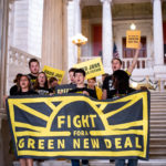 "a group of people in Sunrise shirts holding a banner reading ""Fight for Green New Deal"""